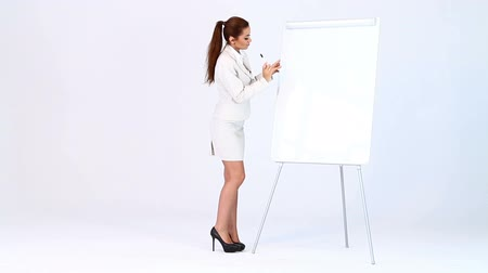 kobieta biznes : Adorable business woman showing two points at blank flipchart Wideo