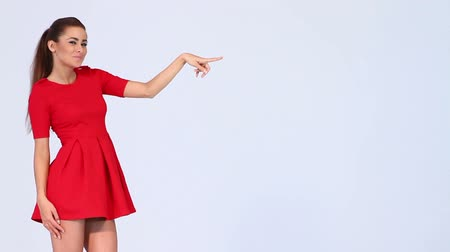 Young attractive woman in red sexy dress pointing at copy space