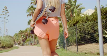 deskorolka : Rear View of a Woman Carrying Skateboard