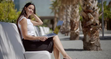 ül : Attractive woman sitting on a bench with a laptop