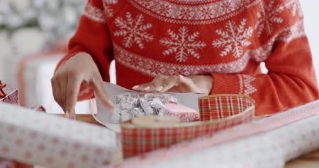 подарок : Young woman carefully wrapping a Christmas gift Стоковые видеозаписи