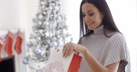 подарок : Young woman opening a Christmas gift bag