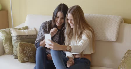 в чате : Two excited young woman reading an sms Стоковые видеозаписи