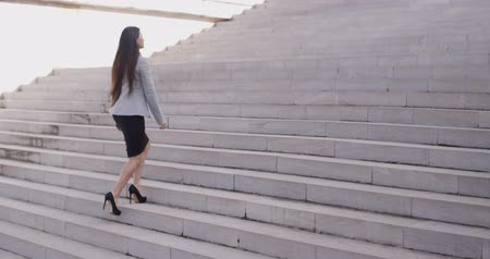 schody : Serious woman walking up staircase Wideo