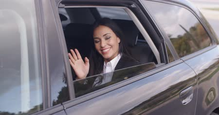 executivo : Cute business woman sitting in car waving hand