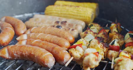 grillowanie : Sausages  corn and veggie kebabs on a BBQ