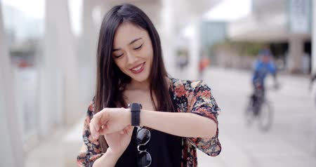 smile : Young woman looking at the time with a smile