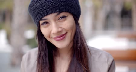 smile : Pretty thoughtful young woman in a woolly cap