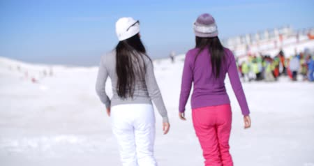 esqui : Two young woman walking in a winter ski resort Stock Footage