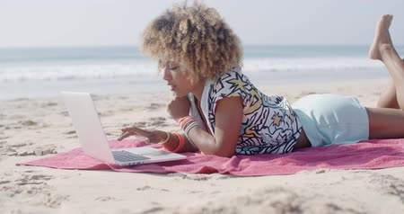 компьютер : Woman On The Beach Using A Computer Стоковые видеозаписи