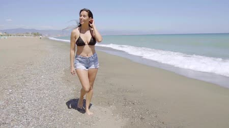bra : Relaxed pretty woman strolling along a beach