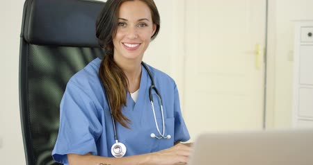 uniforme : Beautiful female doctor at laptop computer