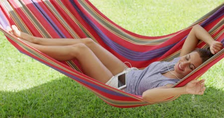 гамак : Happy young woman relaxing in a colorful hammock