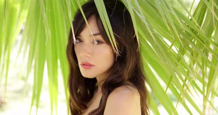 shy girl : Shy young woman in shade of palm leaves Stock Footage
