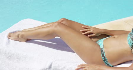 bronzeada : Tanned legs of a young woman sunbathing
