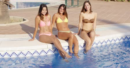 uç : Three happy women sitting on the side of a pool