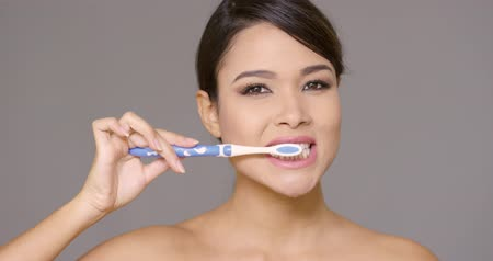 зубы : Smiling friendly young woman brushing her teeth