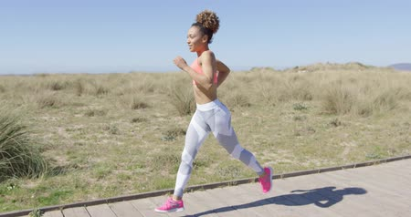 fit : Pretty woman jogging on a pavement Stock Footage