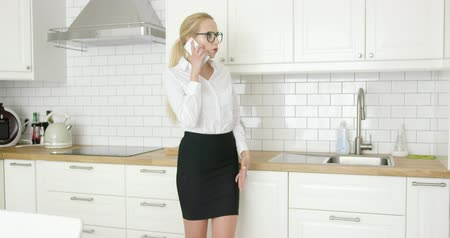 apartamentos : Beautiful confident woman in formal outfit and glasses talking by smart phone while standing at modern kitchen. Stock Footage
