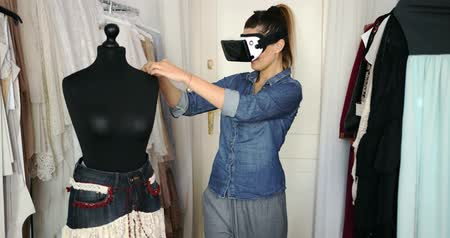criar : Young casual female tailor wearing VR headset and working in parlour with mannequin. Vídeos