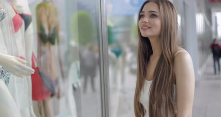 side window : Side view of young woman standing in front of shop window with mannequins and smiling while looking at clothing Stock Footage