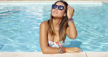 okulary przeciwsłoneczne : Stylish young woman in sunglasses and bikini standing in the cool water at the edge of a swimming pool looking off to the side with a serious expression.