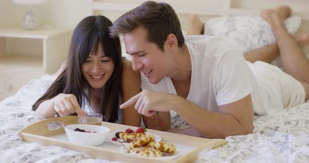 ležící : Attractive young newlywed man and beautiful woman giggling while having breakfast in bed with tray of pastries and bowl of fruit Dostupné videozáznamy