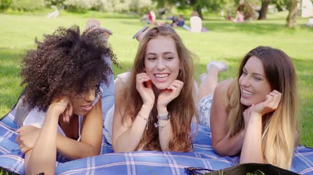três : Three young pretty black and white girls talking and smiling lying on plaid in the park.