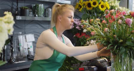 kötény : Side view of female employee in green apron working in floral shop and arranging flowers in bouquets.