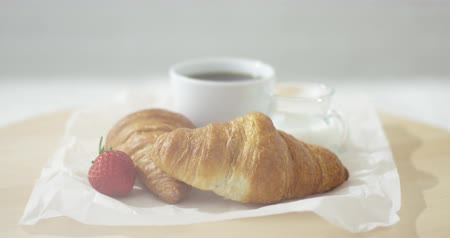kruvasan : Close-up view of delicious croissants on plate with cup of coffee.