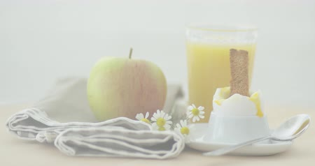 soft boiled egg : Close-up shot of soft-boiled egg with slice of toast served with apple and glass of orange juice. Stock Footage