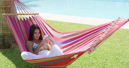 гамак : Beautiful single young woman in white pants and bikini top laying down in hammock while using phone