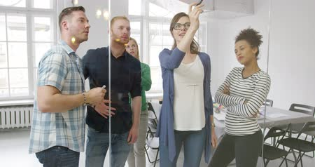 human interest : Diverse group of young casual people talking with interest while posing in modern office and drawing new strategy on glass wall.