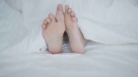 ayaklar : Crop shot of woman lying under cozy white blanket in bed sticking out feet while sleeping and relaxing.
