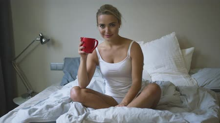 deslumbrante : Beautiful young woman holding mug with hot beverage and looking at camera while sitting on comfortable bed.