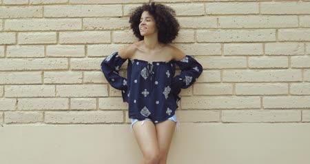 coquettish : Content coquettish girl with short curls posing in trendy shirt and shorts standing with hands on waist looking at camera. Stock Footage