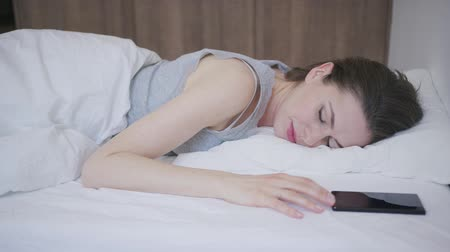 minder : Young beautiful female waking up in bed and looking at smartphone. Stok Video