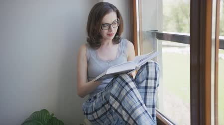 livro : Young beautiful female in eyeglasses and pajamas sitting on window sill at home and reading book.
