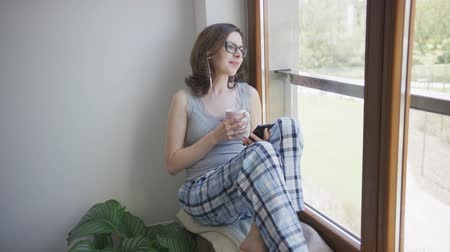 sill : Attractive female in eyeglasses and pajamas sitting on window sill holding mug and using smartphone with earphones.