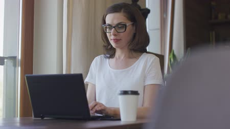 espetáculos : Young beautiful female in eyeglasses sitting at home before laptop and using smartphone. Stock Footage