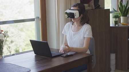interactive table : Young female in virtual reality headset sitting at home before laptop and holding remote controller.