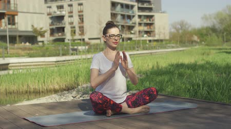 mantra : Beautiful female in glasses meditating in lotus position on exercise mat in summer