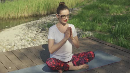 sufferance : Attractive female in glasses with close eyes doing yoga on exercise mat