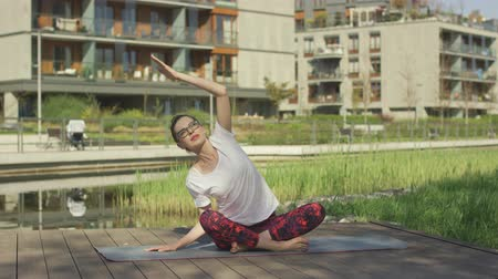 sufferance : Young sporty female doing yoga stretching exercise sitting on mat Stock Footage