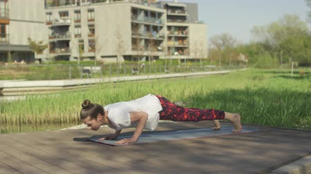 sufferance : Side view of brunette training yoga pose on mat in morning sunlight near water