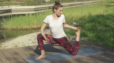 sufferance : Attractive young female doing yoga on exercise mat in morning at park Stock Footage
