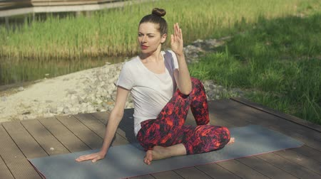 sufferance : Attractive brunette doing yoga twist in morning sunlight near grass Stock Footage