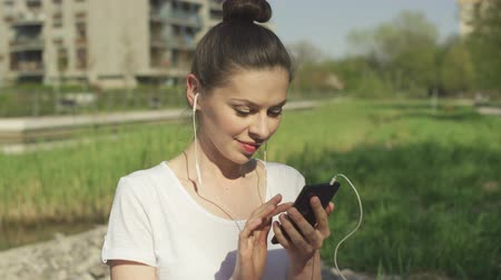 playlist : Concentrated woman listening music on headphones and using smartphone in park