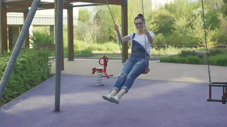 overall : Attractive young female in eyeglasses swinging on playground in city park.