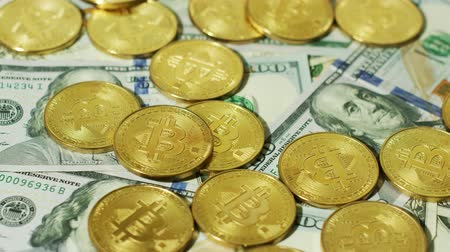 monety : Close-up view of golden coins with sign of bitcoin cryptocurrency arranged on top of new US dollar bills.